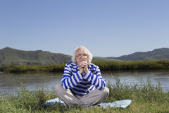 Elderly man sitting on a river bank Stock Image