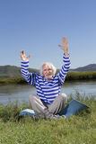 Elderly man sitting on a river bank Stock Images