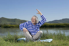 Elderly man sitting on a river bank Stock Photos