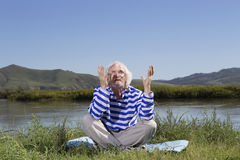 Elderly man sitting on a river bank Royalty Free Stock Images