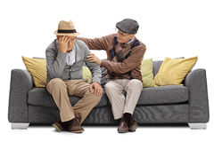 Elderly man sitting on a sofa and comforting another man Royalty Free Stock Image