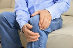 Senior man with pain in knee. Elderly man sitting on a sofa in the living room at home and touching his knee by the pain stock photos