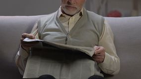 Elderly man sitting on sofa and reading newspaper article, printing media stock video footage