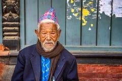 Elderly man sitting in the street of Kathmandu, Nepal Stock Images