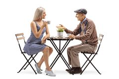 Elderly man sitting at a table and talking to a young woman drinking coffee stock image