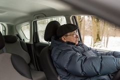 An elderly man is sitting at the wheel of a car. Active old age. Winter, day Royalty Free Stock Photo