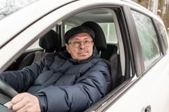 An elderly man is sitting at the wheel of a car. Winter, day Royalty Free Stock Images