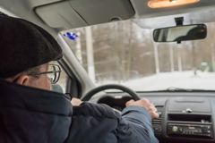 An elderly man is sitting at the wheel of a car. Winter, day Royalty Free Stock Photography