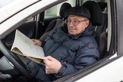 An elderly man is sitting at the wheel of a car. The pensioner r. Eviews the road map and chooses a route for the trip. Active old age. Winter, day Stock Image