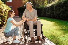 An elderly man is sitting in a wheelchair. The girl crouched beside him, she watches him. An elderly men is sitting in a wheelchair. The girl crouched beside Royalty Free Stock Photo