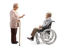 Elderly man sitting in a wheelchair and listening to a senior woman talking and standing with a cane. Full length profile shot of an elderly men sitting in a royalty free stock image