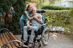 An elderly man is sitting in a wheelchair. Nearby is his daughter and embraces the old man. An elderly men is sitting in a wheelchair. Nearby is his daughter Stock Image