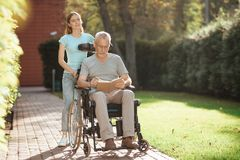 An elderly man is sitting in a wheelchair. Nearby is his daughter, she stands next to the old man`s stroller. An elderly men is sitting in a wheelchair. Nearby Royalty Free Stock Images