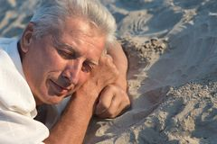 Elderly man sleeping on the sand. In the summer Stock Image