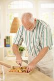 Elderly man slicing up pizza. Elderly man slicing up pizza, standing in living room Stock Photography