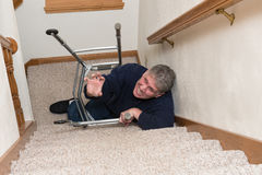 Elderly Man Slip Fall Home Accident. An old mature senior elderly woman has had a slip and fall on a stairway with his medical aid walker. The stairs are a Royalty Free Stock Photos