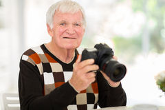 Elderly man SLR camera Stock Images
