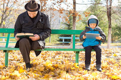 Elderly man and small boy sharing a park bench Stock Photos