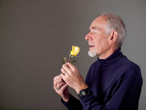 Elderly man smelling a beautiful rose Stock Photo