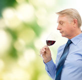 Elderly man smelling red wine. Alcohol and beverage concept - elderly man smelling red wine Royalty Free Stock Images