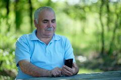 Elderly man smiling as he reads an sms Stock Photography