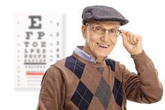 Elderly man smiling in front of an eye chart Stock Photography