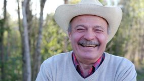 Elderly man smiling outdoors in nature. Elderly man in hat laughing and smiling outdoors in nature stock video footage