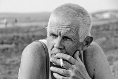 An elderly man smokes. In nature. He is thoughtful and lonely Stock Images