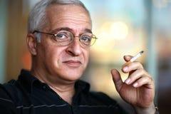 Elderly man smoking cigarette. Royalty Free Stock Images