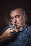Elderly man smoking a pipe Stock Photography