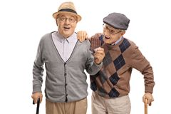 Elderly man sneaking up on another elderly man to grab a bite of. Elderly men sneaking up on another elderly men to grab a bite of his chocolate isolated on Royalty Free Stock Photo