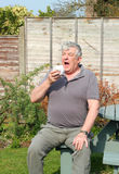 Elderly man sneezing in garden. Royalty Free Stock Images