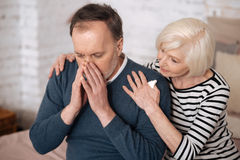 Elderly man sneezing near wife Royalty Free Stock Image