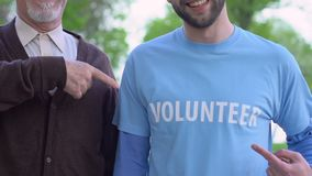 Elderly man and social worker pointing finger at t-shirt with volunteer logo