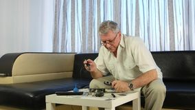 Elderly man soldering a board with a soldering iron, he has in his hands a large magnifying glass. Elderly man is sitting on the couch, before him there is a stock footage