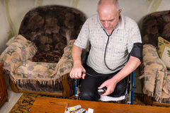 Elderly Man with Special Needs Checking his BP Stock Photography
