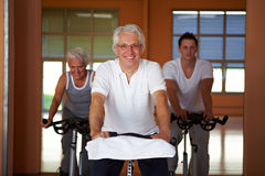 Elderly man on spinning bike Stock Photos