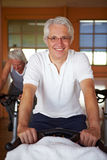 Elderly man on spinning bike. In a gym royalty free stock photography