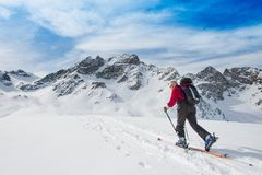 Elderly man sporting fit skis uphill climbing Royalty Free Stock Image