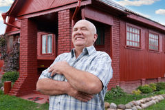 Man standing near red house Stock Photography