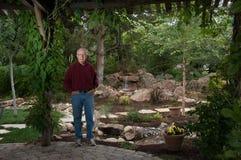 Elderly man standing in his garden Royalty Free Stock Image
