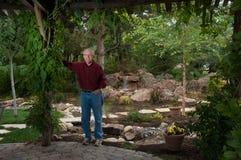 Elderly man standing in his garden Royalty Free Stock Photos