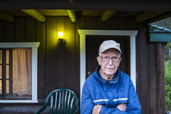 Elderly man standing near a cabin Stock Image