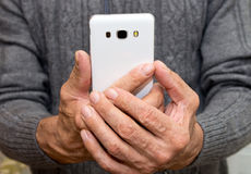 Elderly man standing with a white mobile phone. In hands Stock Photos
