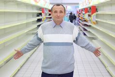 Elderly man stands between empty shelves in shop Stock Photo
