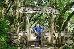An Elderly man stands at the entrance to a long route in a yew-Box grove in the Khostinsky district of Sochi. The inscription in