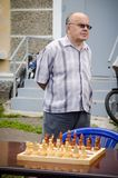 Elderly man stands near the chess table waiting for his opponent in amateur competitions. Komsomolsk-on-Amur, Russia - August 1, 2016. Public open Railroader`s royalty free stock image