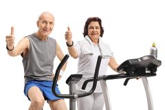 Elderly man on a stationary bike and an elderly woman on a tread. Elderly men on a stationary bike and an elderly women on a treadmill holding their thumbs up Stock Photography
