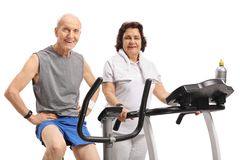 Elderly man on a stationary bike and an elderly woman on a tread. Elderly men on a stationary bike and an elderly women on a treadmill isolated on white Stock Image