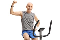 Elderly man on a stationary bike flexing his biceps. Isolated on white background Royalty Free Stock Photography